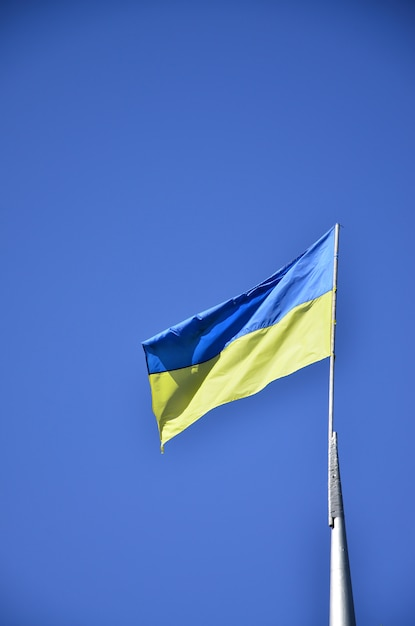 Ukrainian flag against the blue cloudless sky. the official flag of the ukrainian state includes yellow and blue colors Premium Photo