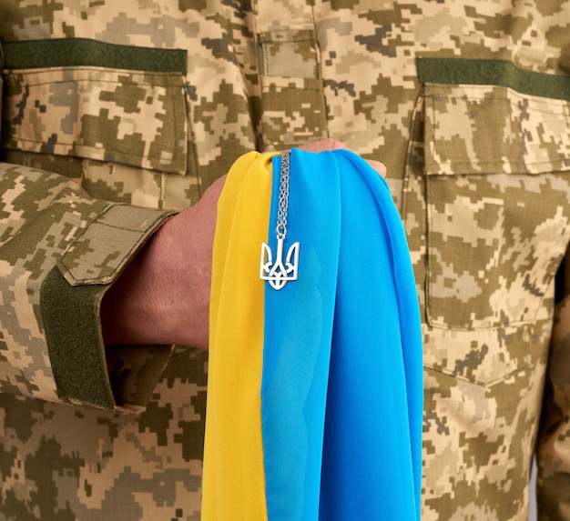 Украинский воин, одетый в военную пиксельную форму, держит желто-синий флаг государства украина и на цепочке маленький герб страны трезубца Premium Фотографии