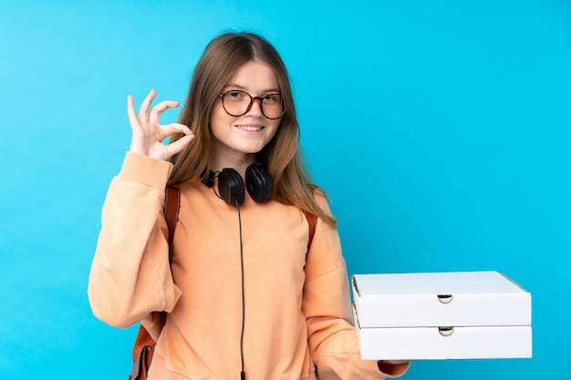 Ukrainian teenager girl holding pizzas over isolated blue wall showing ok sign with fingers Premium Photo