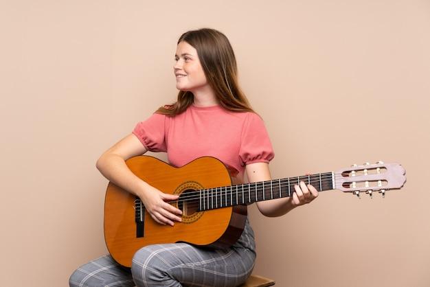 Ukrainian teenager girl with guitar over isolated  looking side Premium Photo