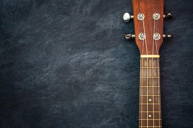 Ukulele on black cement. headstock and fret of ukulele parts. Premium Photo