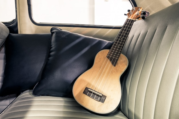 Ukulele on seat vintage car Premium Photo