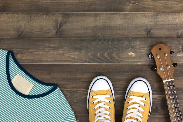 Ukulele, shirt and shoes on old wooden background with copy space. flat lay Premium Photo