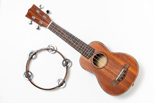 Ukulele and wooden tambourine on white Premium Photo