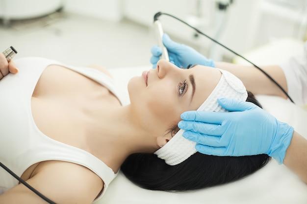 Ultrasonic face cleaning, peeling, in a beauty salon Premium Photo