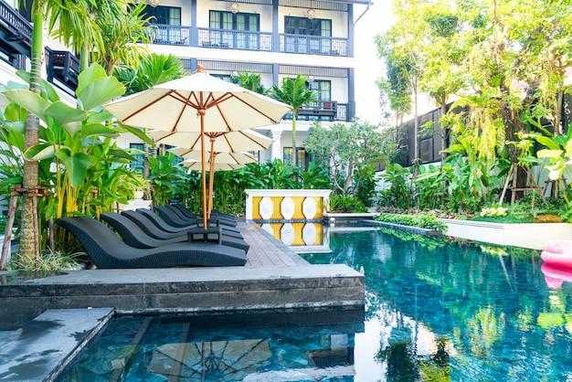 スイミングプールの周りの傘とベッドプールチェア-休暇と旅行の休日のコンセプト Premium写真