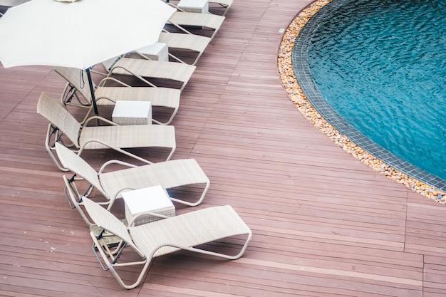 傘とスイミングプールの周りの椅子 無料写真