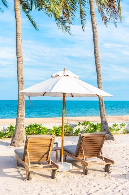 바다 바다 해변과 코코넛 야자 나무가있는 호텔 리조트의 야외 수영장 주변의 우산과 갑판 의자 무료 사진