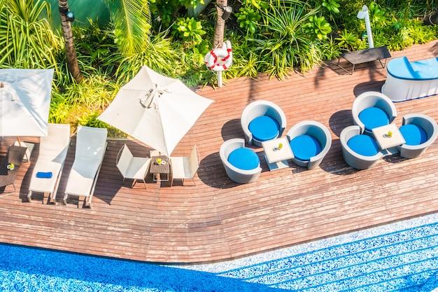 Umbrella and chair around beautiful luxury swimming pool Free Photo