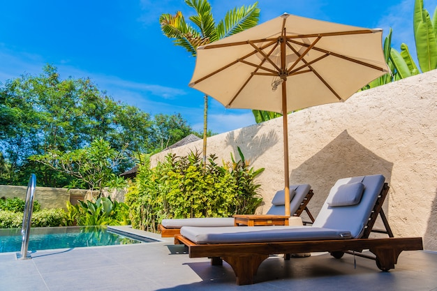 Umbrella and chair around swimming pool neary sea ocean beach with blue sky and white cloud Free Photo
