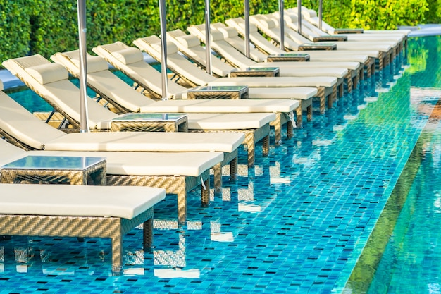 Umbrella and chair sofa around outdoor swimming pool in hotel resort for holiday vacation Free Photo
