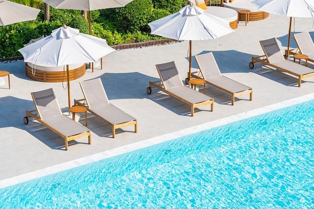 Ombrellone e sdraio intorno alla piscina all'aperto nel resort dell'hotel quasi mare spiaggia oceano Foto Gratuite