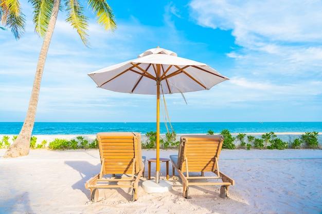 Ombrellone e sdraio intorno alla piscina all'aperto nel resort dell'hotel con spiaggia sull'oceano e palme da cocco Foto Gratuite