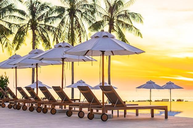 日没時または日の出時に海の海のビーチとココナッツ椰子の木があるホテルリゾートのスイミングプールの周りの傘デッキチェア 無料写真