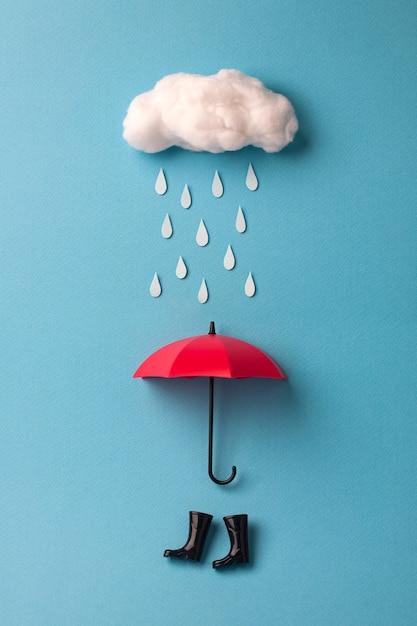 Umbrella and rain boots under the cloud on sky blue Premium Photo