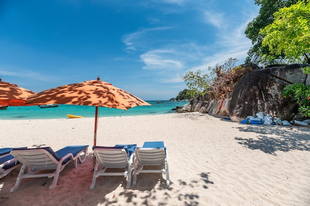 Umbrella with sunbed on the white beach in tropical sea Premium Photo