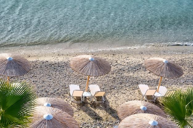 Halkidiki, 그리스의 Fourka Scala 해변에서 우산과 일광욕 침대 프리미엄 사진