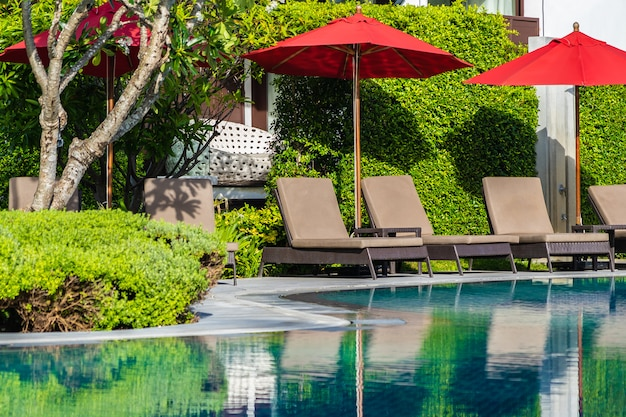 Umbrellas and deck chairs around outdoor swimming pool Free Photo