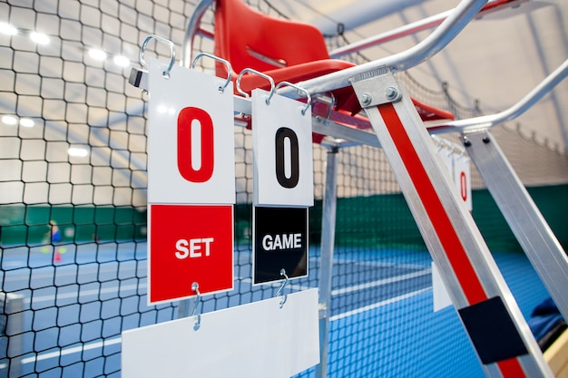 Umpire chair with scoreboard on a tennis court before the game Free Photo