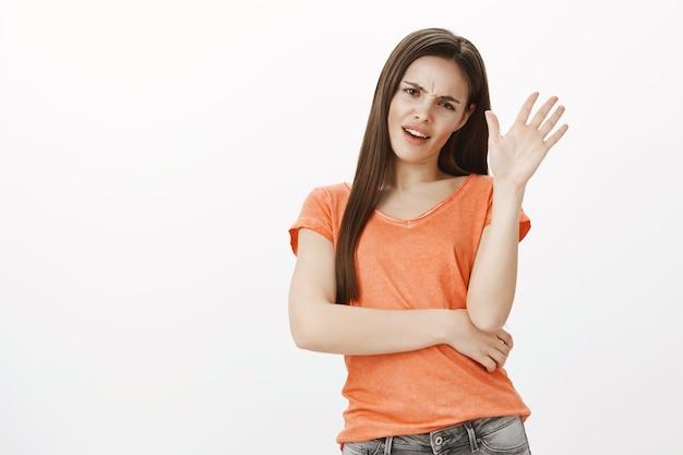 面白がって面倒な生意気な女の子が申し出を拒否し、拒否で手を振って、申し出が嫌いで、何かを否定している 無料写真
