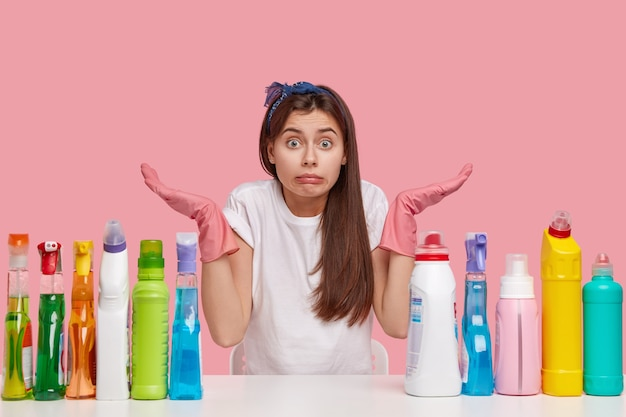 알지 못하는 청소부 소녀는 분홍색 고무 보호 장갑을 끼고 망설임으로 손을 펴고 청소 세제로 흰색 책상에 포즈를 취하고 어떤 방을 먼저 정리할지 결정할 수 없습니다. 가사 개념 무료 사진