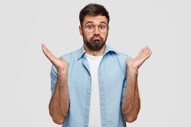 Невежественный бородатый красавец неуверенно пожимает плечами Бесплатные Фотографии
