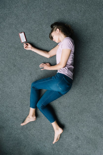 Unconscious woman lying on carpet near mobile phone Free Photo