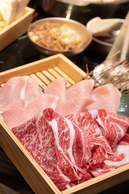 Uncooked fresh sliced pork and beef put in a wooden square box that preparing for shabu Premium Photo