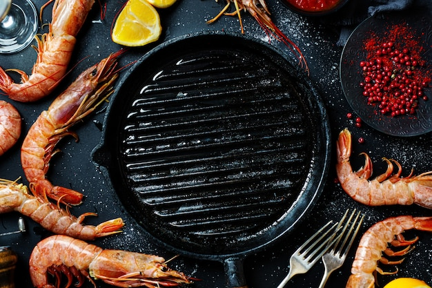 Uncooked giant shrimps on dark table Free Photo