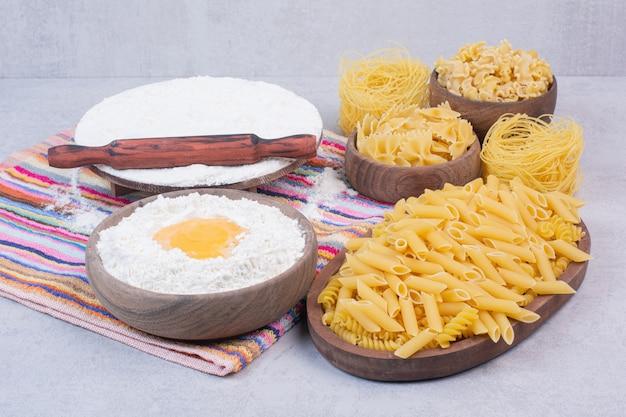 노른자와 밀가루를 곁들인 나무 그릇에 익히지 않은 마카로니 무료 사진