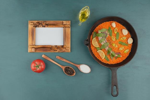 赤レンズ豆、ペッパースライス、ニンニク、ほうれん草を額縁と油で黒鍋に入れた未調理の肉。 無料写真