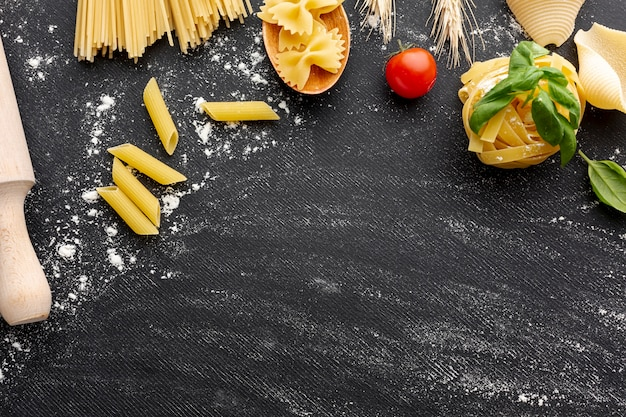 Uncooked pasta arrangement frame on black background with copy space Free Photo