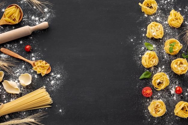 黒い背景に小麦粉と調理パスタの品揃え Premium写真