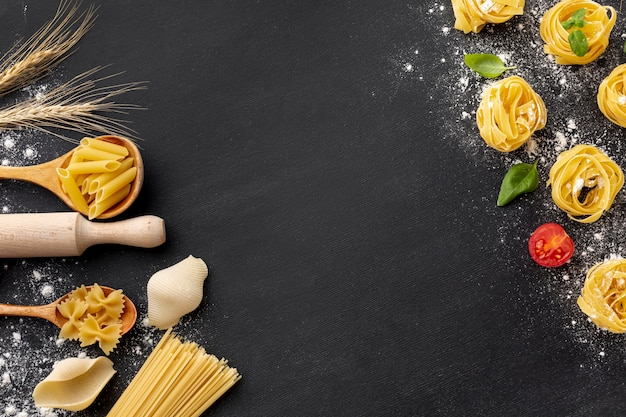 Uncooked pasta assortment with flour and rolling pin on black background Free Photo