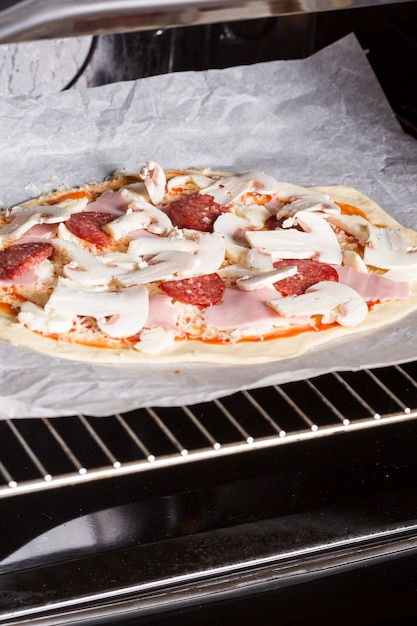Uncooked pizza on parchment paper placed in the oven Free Photo
