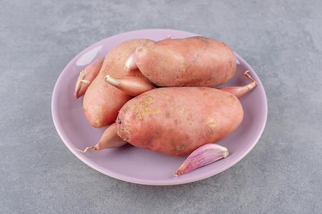 紫色のプレートにニンニクが入った未調理のジャガイモ。 無料写真
