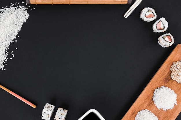 Uncooked rice; chopsticks; sushi and soya sauce on black background Free Photo