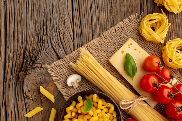 Uncooked spaghetti cellentani penne tomatoes and hard cheese Free Photo