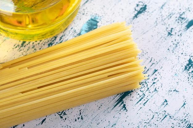 Pasta cruda degli spaghetti con la bottiglia di olio su bianco. Foto Gratuite