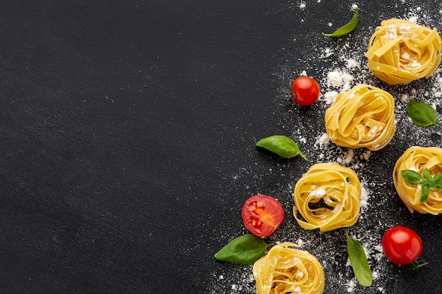 Uncooked tagliatelle on black background with tomatoes basil with copy space Free Photo