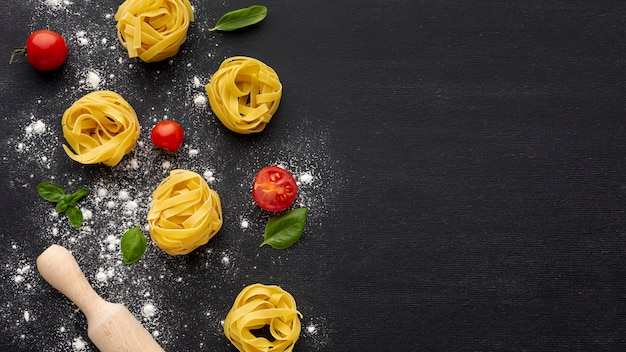 Uncooked tagliatelle on black background with tomatoes rolling pin and copy space Free Photo