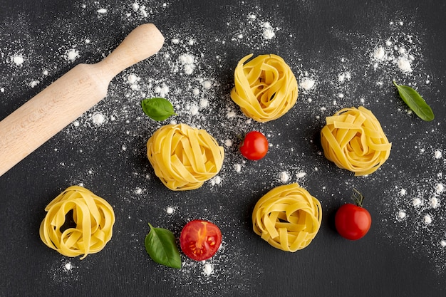 Uncooked tagliatelle on black background with tomatoes and rolling pin Free Photo