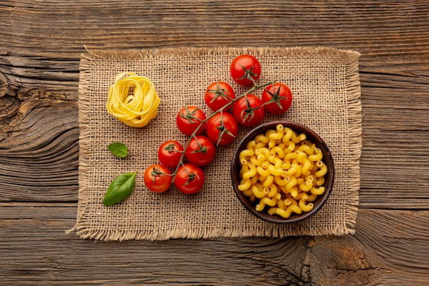 Uncooked tagliatelle and cellentani with tomatoes Free Photo