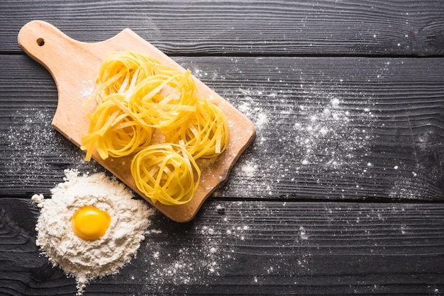 Uncooked tagliatelle on chopping board with egg york in flour on wooden plank Free Photo