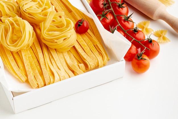 Uncooked tagliatelle fettuccine and tomatoes Free Photo