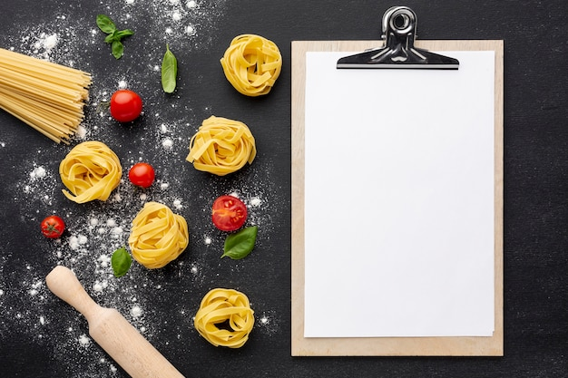 Uncooked tagliatelle spaghetti on black background with tomatoes rolling pin and clipboard mock-up Free Photo