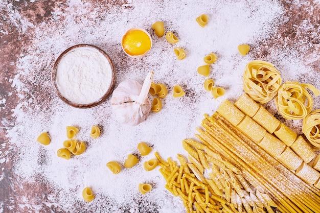 木製のテーブルに小麦粉を入れた未調理の様々なパスタ。 無料写真