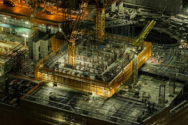 未定義の労働者が建設中で、クレーンが建物を建設 Premium写真