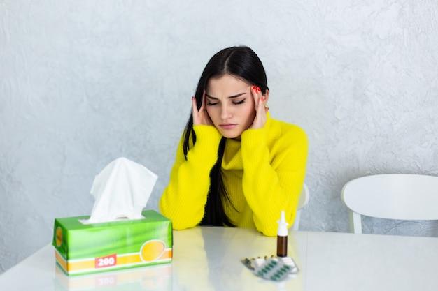天気の下で。病気の若い女性が気分が悪く、彼女の肩に毛布を持ち、目を閉じて丸薬を彼女の前に置いた状態でソファに座っている間に鼻をかむ 無料写真
