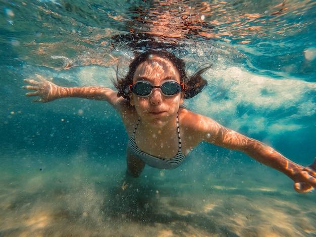 Underwater photo of girl swimming in the sea Premium Photo
